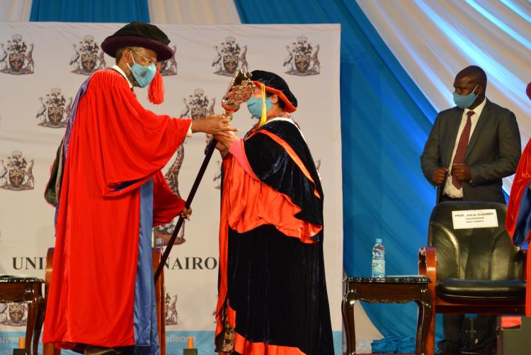 Prof. Kiama receiving the University of Nairobi maise symbol of our scholarly integrity